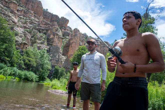 Edgar Mareno, left, and Las Cruces City Councilor Gabe Vasquez watch Manuel Avila fish in the Gila Wilderness on Friday, Aug. 3, 2019.