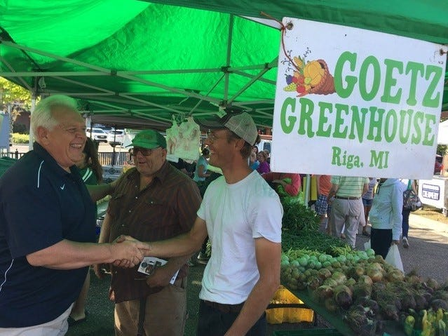 CARES Director Todd Lipa gives off a joyous smile partnering with a local farmer at the market helping those in need of direct access to fresh local produce.  Steve Goetz extends a hand of partnership while father Jon Goetz looks on.