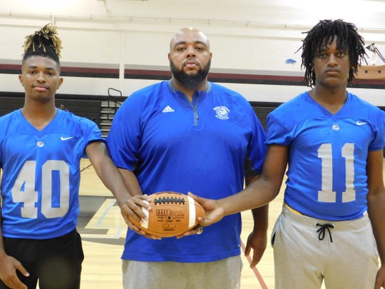 North Central football players Christopher Rideau (40) and Aaron Johnson (11) are pictured with head coach Jacob Thierry.