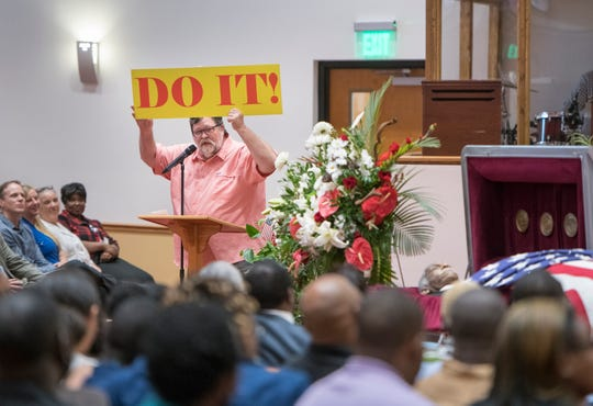 Friend and real estate colleague Audie Street holds up a sign with late Pensacola City Councilman Gerald C. Wingate's favorite slogan during a public memorial Wednesday at St. John Divine Missionary Baptist Church in Pensacola