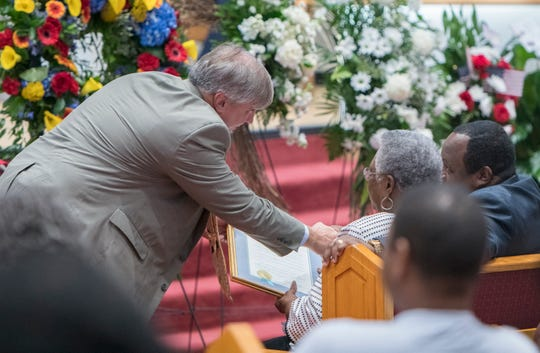 Pensacola Mayor Grover Robinson presents a city proclamation to Betsie Wingate, the widow of Gerald Wingate, during a public memorial for the late Pensacola City Councilman on Wednesday at St. John Divine Missionary Baptist Church in Pensacola.