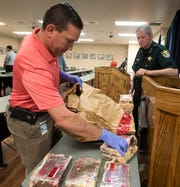 Escambia County Sheriff David Morgan looks on as Sgt. Brandon Beech collects bricks of powdered cocaine to be returned to evidence storage after a press conference Thursday. The ECSO seized 22 kilos of powdered cocaine during a recent drug bust.