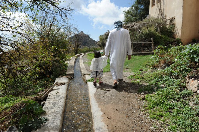 Mahmoud bin Mohammed al-Riyami, a farmer, holds the hand of his 4-year-old daughter, Fatima, while walking beside an aqueduct in A'Sherageh, Oman.