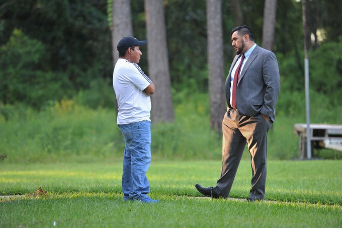 Ray Ybarra Maldonado (right), a Phoenix attorney specializing in immigration law, talks with his client about his wife's case while standing in the yard of St. Michael's Catholic Church in Forest, Mississippi, Aug. 28. 2019. The man's wife was taken during the Aug. 7, 2019, U.S. Immigration and Customs Enforcement raid at the Koch Foods plant in Morton, Mississippi. The couple have three children, the youngest 7 months old. At the time of his wife's detainment, she had been nursing.