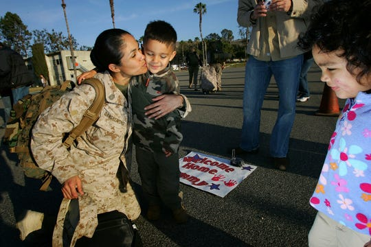 Una mujer miembro del ejército de Estados Unidos es recibida por su pequeño hijo. Foto archivo.