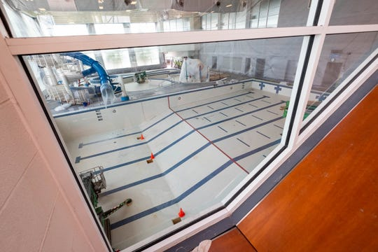 The walls and some of the equipment in the pool area at the YMCA are covered in plastic sheeting during renovations. The pool area is having the ceiling repainted and LED lighting installed, the ducts cleaned, new pumps installed, and the slide is being reconditioned.
