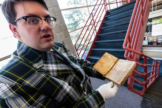 Andrew Kercher, Port Huron Museum manager of community engagements, wears gloves while handling John Riley's New Testament at the Port Huron Museum Thursday, Aug. 29, 2019.
