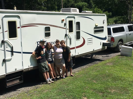 Members of the Tompkins family, left to right, Gaetono, Josie, Kimberlee and Billy, stand next to their 33-foot camper trailer.