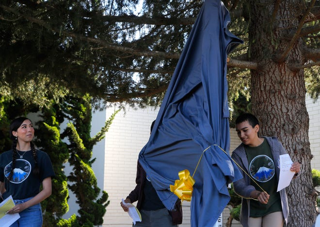 Alyssa Powell, 18, looks on as Bryanna Mendez, 18, unveils the Salinas City Hall Peace Pole, which the students raised money for after a trip to Okinawa last year with the Salinas Union High School District's Japanese Program.