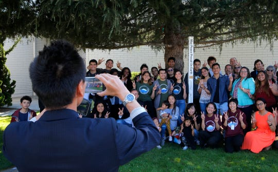 Students, teachers and officials pose for a picture at the Tuesday unveiling ceremony of the new Peace Pole at Salinas City Hall.