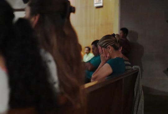 A woman covers her face during the mass for Keyla Salazar. August 28, 2019.