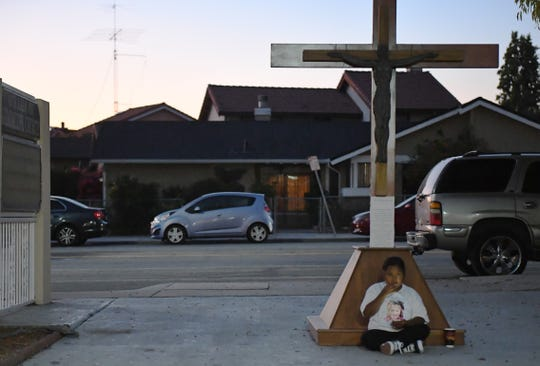 A young relative sits at the base of the cross outside the church during the mass for Keyla Salazar. August 28, 2019.