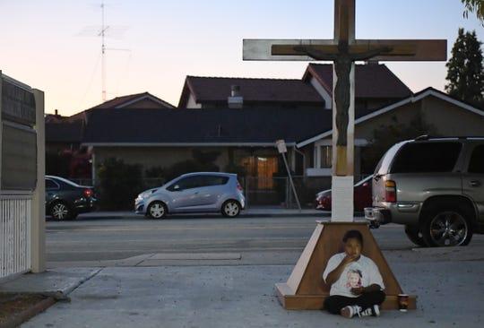 Un joven pariente sentado a los pies de la cruz afuera de la iglesia durante la misa para Keyla Salazar. 28 de agosto de 2019.