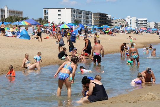 Visitors to the Ocean City beach play in tide pools near 112th Street Thursday, Aug. 29, 2019. The pools form annually each August, spurred by  large waves that are driven further onto the beach by strong winds. Tropical activity in the Atlantic at this time of year can cause larger than usual waves and surf conditions.