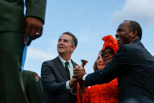 Virginia Gov. Ralph Northam, from left, joins hands alongside his wife Pamela Northam, Professor Marian Clifton and City of Hampton Mayor Donnie Tuck during the bell ringing ceremony for the First African Landing Day commemorative ceremonies at Fort Monroe in Hampton, Va., Sunday, Aug. 25, 2019.