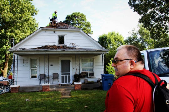 Dale Williams watches as a crew replaces the roof of his home in Clever Wednesday, Aug. 28, 2019.