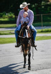 John Logsdon and his son Ian Logsdon, 2, ride Okie the mule at the Ozark Empire Fairgrounds on Thursday, Aug. 29, 2019, in Springfield, Mo. Logsdon and Okie will be competing at the Ozark Mule Days event on Friday, Aug. 30 - Sunday, Sep. 1, at the fairgrounds.
