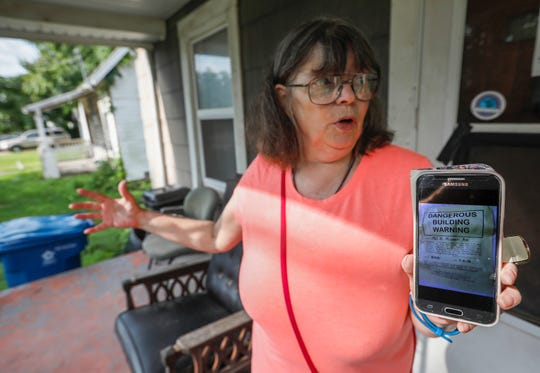 """Kathy Lutz, the president of the Grant Beach Neighborhood Association, displays a photo of the """"Dangerous Building Warning"""" sign that was posted on the home next door to her."""