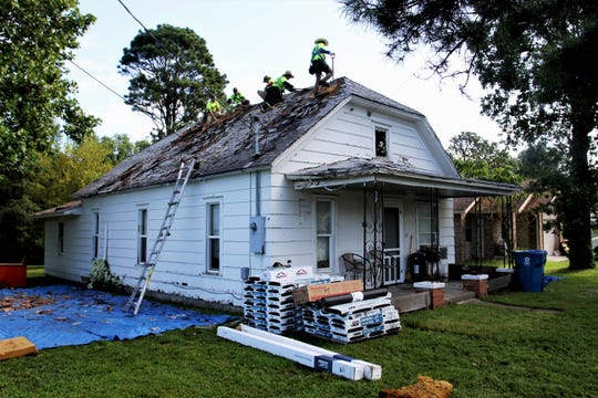 Christian Construction of Missouri workers take off shingles from a roof in Clever Wednesday, Aug. 28, 2019.