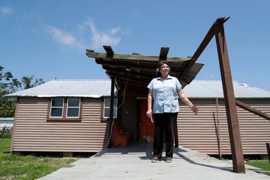 Deborah Peddie stands on what was once her back porch in Bristol, Fla. When Hurricane Michael ripped through the Panhandle her home, like many others, was torn to pieces, littered with debris, and had fallen trees on top of her home.
