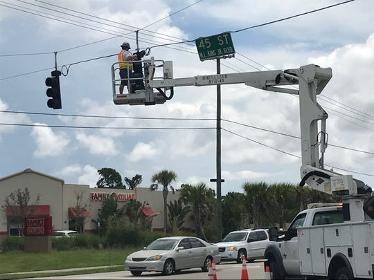 Indian River County Public Works traffic signal technicians remove traffic lights at the intersection of 43rd Avenue and 45th Street Thursday, Aug. 29, 2019. ahead of Hurricane Dorian.