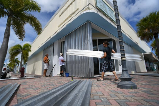 "Property manager Beau Bryan (second from left) along with Mark Lissner (left) and Jason Alfonso, put up shutters in preparation for the arrival of Hurricane Dorian Thursday, Aug. 29, 2019, on the new restaurant Pickled Southern Table and Bourbon along 2nd Street in Fort Pierce. ""Getting ahead of it so we won't have to do last minute things,"" Bryan said."