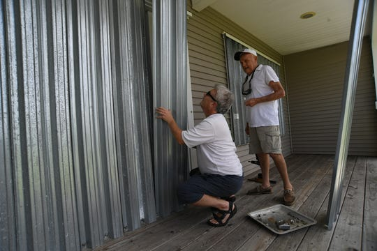 "Barry Kowalik (left) of Danville, Kentucky, helps his father Frank Kowalik board up his manufactured home on Silvery Lane on Thursday, August 29, 2019, in the Fairlane Harbor neighborhood of Vero Beach, in preparation for the arrival of Hurricane Dorian. ""I'm glad to be able to be down here, he wouldn't be able to do this by himself,"" Barry Kowalik said. The pair were using metal panels for hurricane protection on Frank's home along Indian River Boulevard.  ""It sucks, it's going to be a biggie,"" Frank Kowalik said."