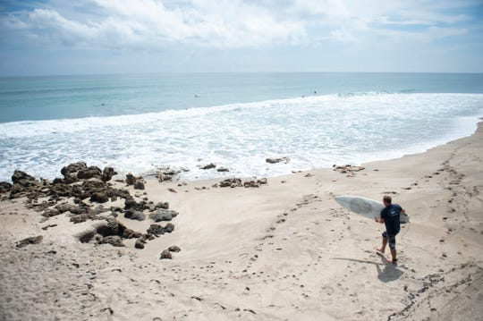 Surfers search for waves ahead of Hurricane Dorian on Thursday, Aug. 29, 2019, at Chastain Beach on Hutchinson Island.
