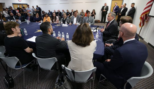 Texas Gov. Greg Abbott, right, sits with families of victims and survivors of the Aug. 3, 2019, shooting at Walmart in El Paso, Texas, on Thursday, Aug. 29, 2019. About 30 representatives from law enforcement and nongovernmental agencies were at the roundtable discussion on public safety.