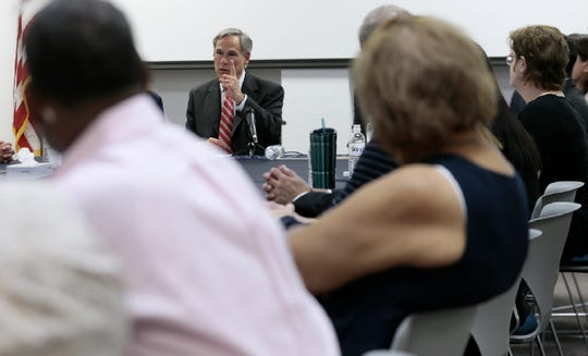 Texas Gov. Greg Abbott talks with families of victims and survivors of the Aug. 3, 2019, shooting at Walmart in El Paso, Texas, on Thursday, Aug. 29, 2019. About 30 representatives from law enforcement and nongovernmental agencies were at the roundtable discussion of public safety.