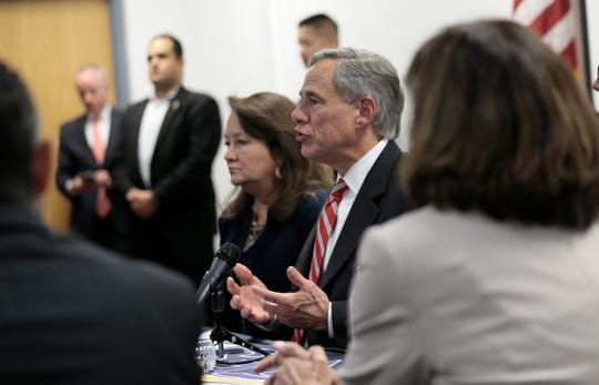 Texas Gov. Greg Abbott sits with families of victims and survivors of the Aug. 3, 2019, shooting at Walmart in El Paso, Texas, on Thursday, Aug. 29, 2019. About 30 representatives from law enforcement and nongovernmental agencies were at the roundtable discussion of public safety.