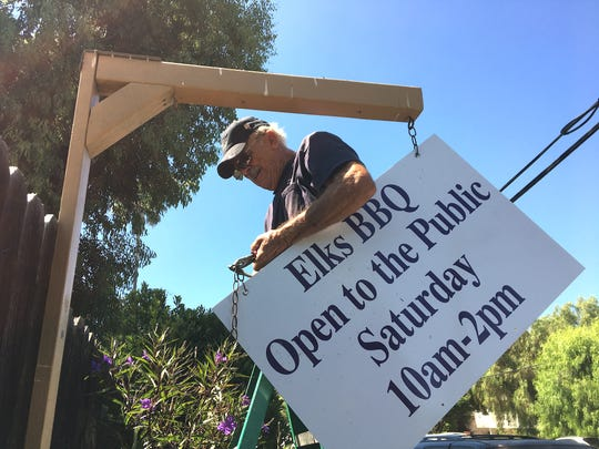 Gerry Gillies prepares to hang a sign announcing the weekly barbecue at the Thousand Oaks Elks Lodge, 158 Conejo School Road.