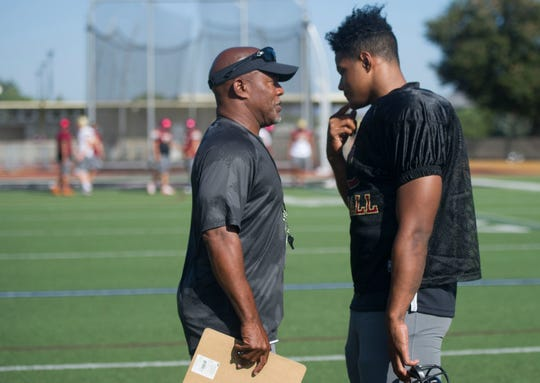 Head coach Charles Collins, left, talks with star player Mister Williams during Oaks Christian's practice on Wednesday.