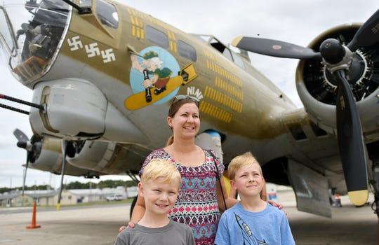 "Stephanie Farmer and her sons, left to right, Nathan and Trevor, pose for a photo in front of the Boeing B-17 Flying Fortress ""Nine-O-Nine"" at the Millville Executive Airport."
