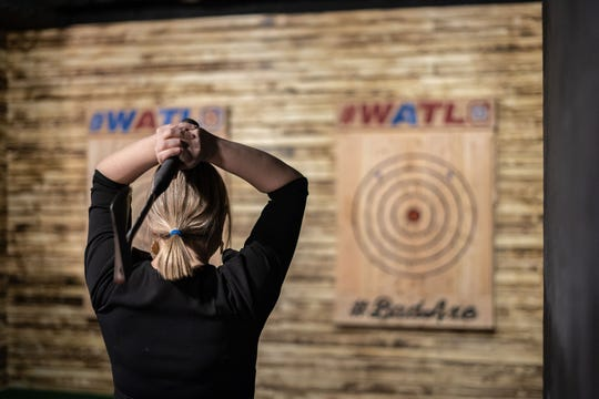 A woman prepares to throw an ax at Bad Axe Throwing.