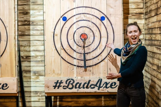 A woman presents her on target throw at Bad Axe Throwing.