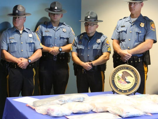 State police officers stand in front of a table of seized drugs.