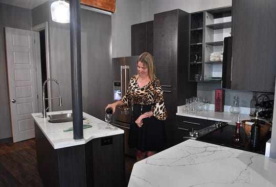 Cynthia Doten pours a glass of wine in the kitchen of her apartment at the 9th Street Lofts.