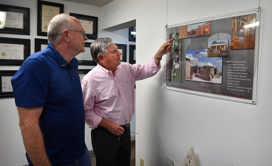 Troy Secord, left, and Jackie Lebow look over a TXDot project their architecture firm worked on. Lebow is retiring after almost 40 years in architecture.