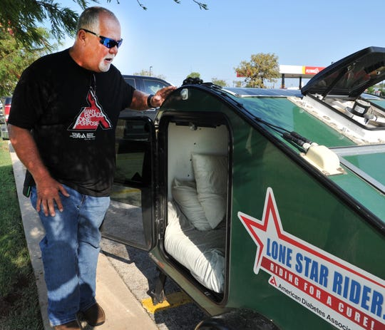 Rex Covington stands near his living quarters, a small motorcycle pulled camper he has called home since beginning his travels raising money for a cure to diabetes.