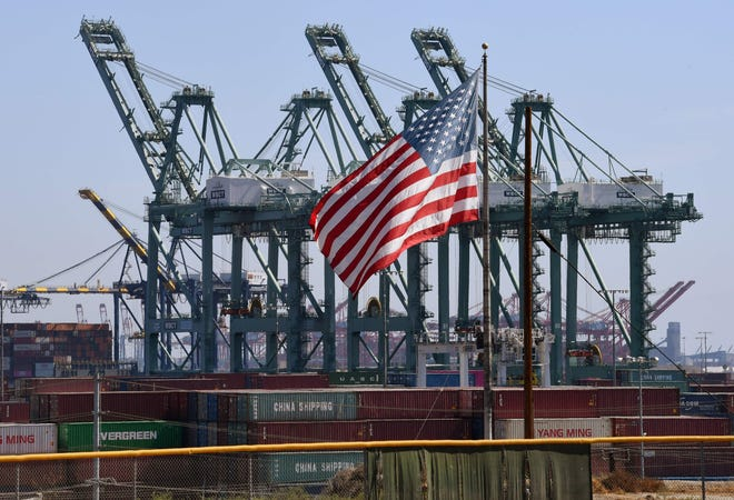 A US flag flies over Chinese shipping containers unloaded at the Port of Long Beach, in Los Angeles County.