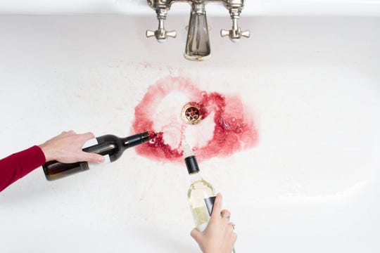 Pouring wine down sink