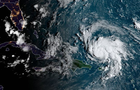 "This satellite image obtained from NOAA/RAMMB, shows Hurricane Dorian (R) as it  passes Puerto Rico at 11:30 central time on August 29, 2019. The National Hurricane Center (NHC) in Miami said the hurricane watch and tropical storm warning for the island had been lifted, and that ""Dorian continues to move away from Puerto Rico and the Virgin Islands."""