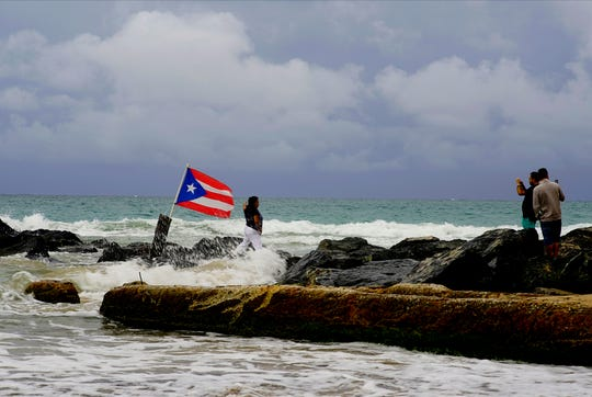 A woman poses for a photograph backdropped by ocean waters and a Puerto Rican national flag, after the passing of Tropical Storm Dorian, in the Condado district of San Juan, Puerto Rico, Wednesday, Aug. 28, 2019.