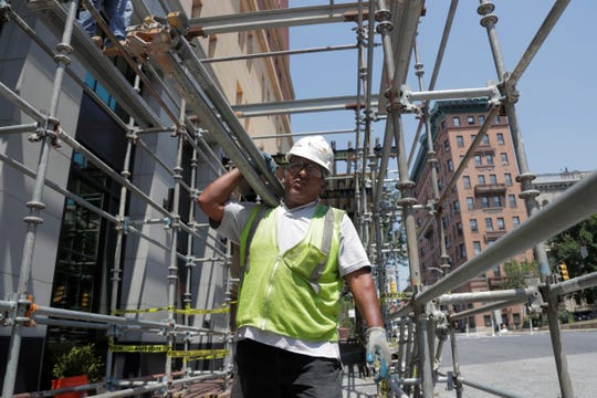 A construction worker helps build scaffolding in Baltimore, Maryland, in August 2019.