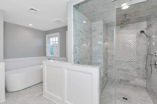 The luxurious master retreat features a stunning new master bath with marble tile work a custom glass-enclosed steam shower and separate tub.