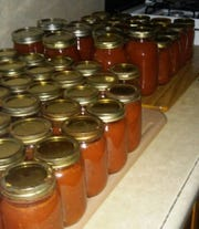 Jars of canned pizza sauce, made with fresh tomatoes from Lovina's garden, ready to be stored for use by the family throughout the year.
