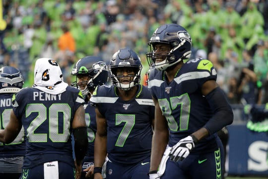 Seattle Seahawks quarterback Geno Smith (7) stands with wide receiver Jazz Ferguson, right, during the first half of an NFL football preseason game against the Oakland Raiders on Thursday.