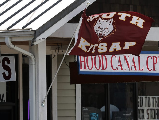 A South Kitsap Wolves flag flutters in the breeze in front of CrossFit NXNW and Hood Canal Carpets on Bay Street in Port Orchard on Thursday.