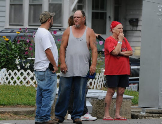 Bucyrus residents gather in a nearby alley on Sept. 2, 2014, as police investigate a death at 218 W. Mansfield St.